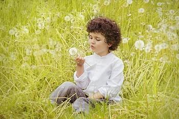 Kid blowing on flower